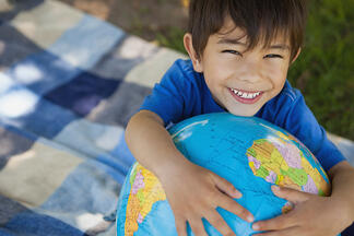 Close-up portrait of a cute young boy holding globe at the park-1