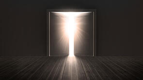 Doors opening to show a bright light in the darkness