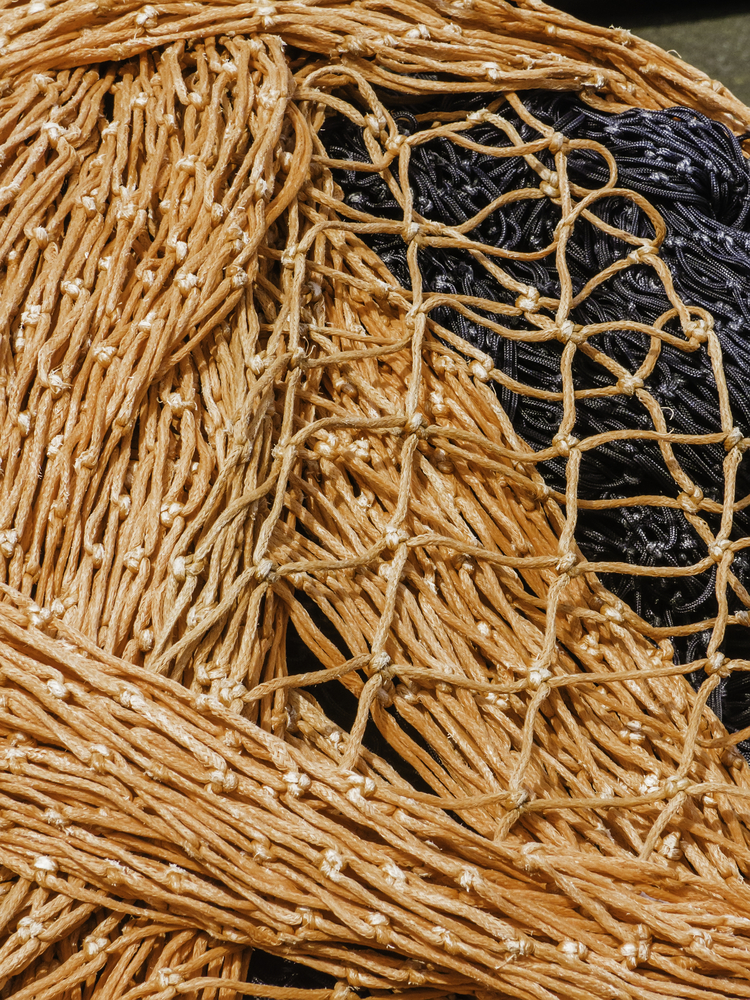Maritime detail Orange and black commercial fishing nets piled together at marina